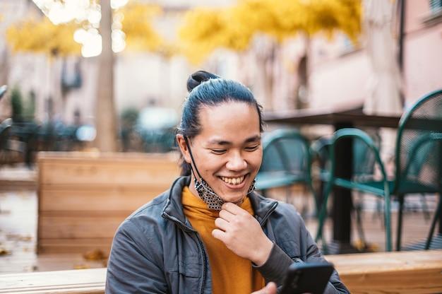 Glücklicher asiatischer mann, der mit offener gesichtsmaske in der coronavirus-zeit lächelt - neues normales lebensstilkonzept durch selbstbewussten mann, der nachrichten auf smartphone ansieht und auf einer bank nahe der straße sitzt