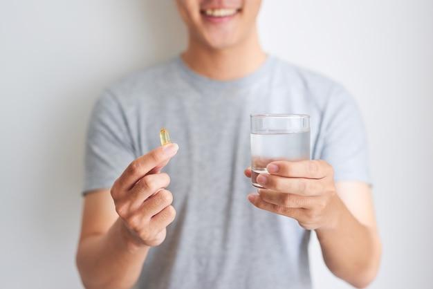Glücklicher asiatischer mann, der zu hause eine omega-3-vitaminpille hält