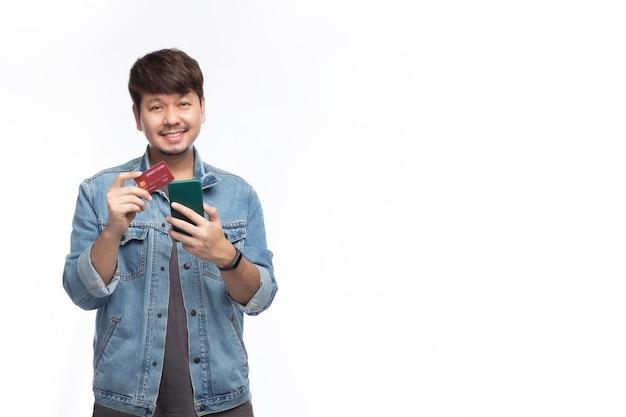 Glücklicher asiatischer mann im smileygesicht, der eine kreditkarte und ein smartphone hält, betrachten die kamera, studiolichtporträt lokalisiert auf weißem hintergrund, kreditkartenkonzept