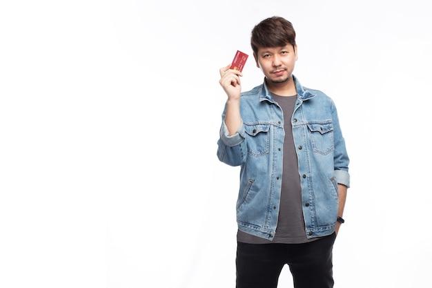Glücklicher asiatischer mann im smileygesicht tragen blaue jeansjacke halten kreditkarte, betrachten kamera, studiolichtporträt lokalisiert auf weißem hintergrund, kreditkartenkonzept