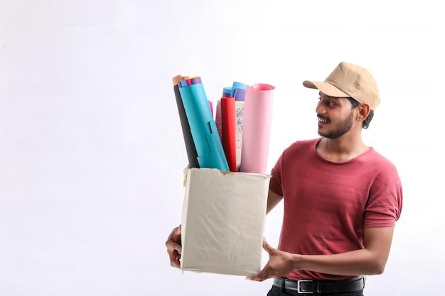 Glücklicher asiatischer mann in t-shirt und mütze mit farbigem papierkasten isoliert auf weißem hintergrund, lieferservice-konzept
