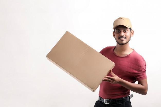 Glücklicher asiatischer mann in t-shirt und mütze mit leerem karton isoliert auf weißem hintergrund, lieferservice-konzept