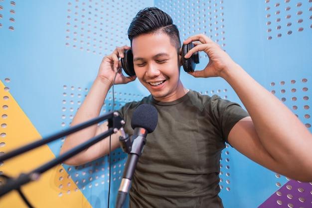 Glücklicher asiatischer mann nimmt in seinem studio einen podcast auf