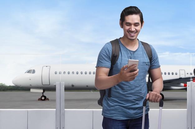 Glücklicher asiatischer mannreisender, der mit tasche und handy steht