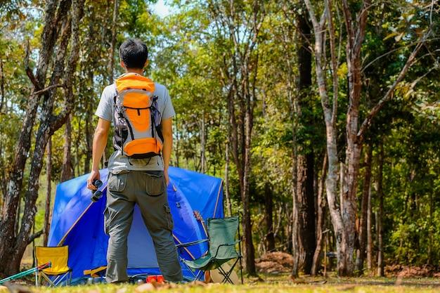 Glücklicher asiatischer mannrucksack im park- und waldhintergrund, entspannen sich zeit auf feiertagskonzeptreise