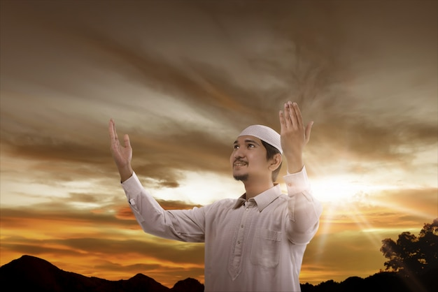 Glücklicher asiatischer moslemischer mann, der zum gott betet