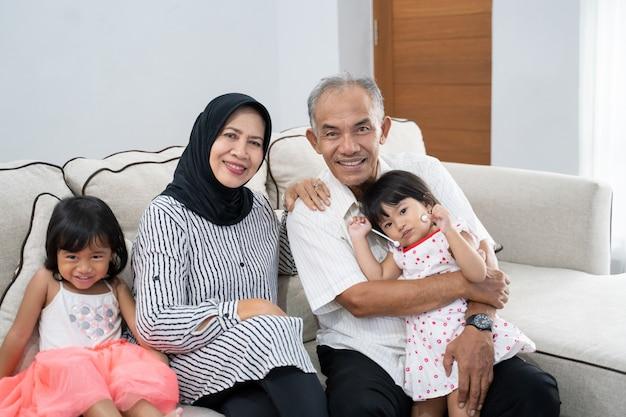 Glücklicher asiatischer muslimischer großelternteil mit ihren enkelkindern zu hause