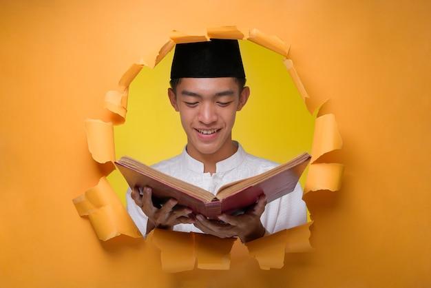Glücklicher asiatischer muslimischer mann, der den heiligen koran hält und muslimisches tuch mit schädelkappe trägt, posiert durch zerrissenes gelbes papierloch und liest den heiligen koran im ramadan kareem