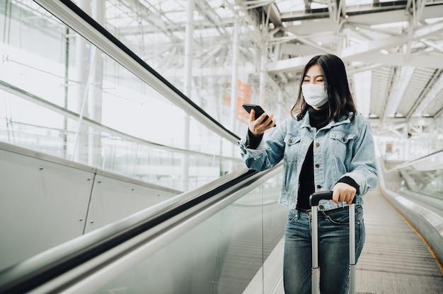 Glücklicher asiatischer reisender, der maske trägt, die smartphone auf rolltreppe steht