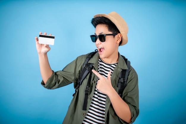 Glücklicher asiatischer rucksacktourist mit kreditkarten