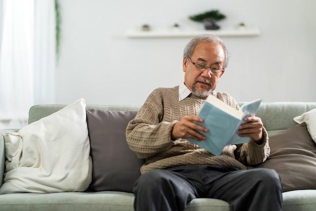 Glücklicher asiatischer ruhestand älterer mann, der auf sofa am wohnzimmer liest, das fiktionsbuch liest.