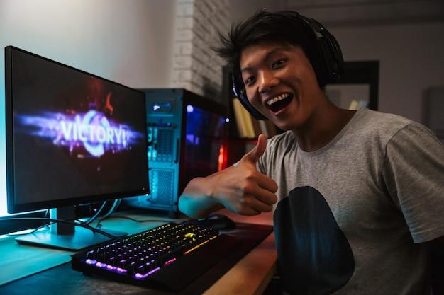 Glücklicher asiatischer spieler 16-18 freut sich über den sieg, während er videospiele am computer in einem dunklen raum spielt, kopfhörer trägt und eine hintergrundbeleuchtete bunte tastatur verwendet