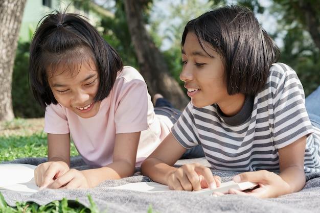 Glücklicher asiatischer student beim lügenlesen des buches auf der decke im sommer