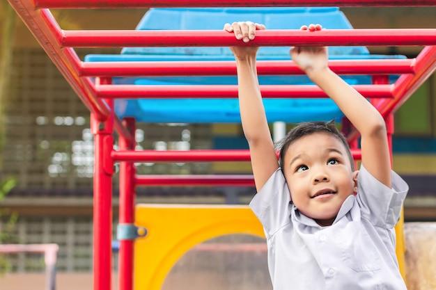 Glücklicher asiatischer student - kinderjunge, der an einer stahlstange auf dem spielplatz spielt und hängt.