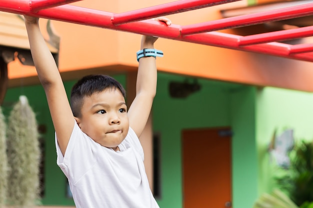 Glücklicher asiatischer studentenkindjunge, der von einer stahlstange am spielplatz spielt und hängt.