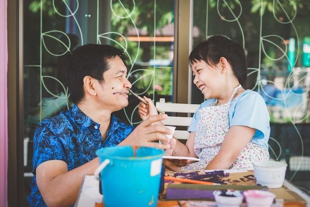 Glücklicher asiatischer vatertag. lustiger lächelnder vater und ihre tochter malen und zeichnen mit aquarell