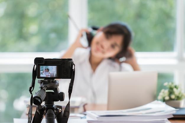 Glücklicher asiatischer videoblog- oder studentenfrauenschönheitsblogger / -logger, der tutorialtrainer-darstellungs-durchlaufvideo für das unterrichten von den livehausaufgaben teilt onlinekanalsocial media durch mirrorless kamera notiert