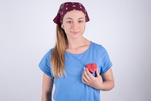 Glücklicher athlet, der eine gesunde rote herzfrequenz hält. die stärke des medizinischen herzens stärkt den lebensstil. weiblich. herzgesundheit und wellness.