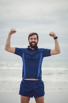 Glücklicher athlet, der mit erhobenen händen am strand steht