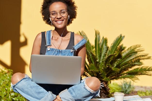 Glücklicher attraktiver afroamerikanischer teenager mit positivem ausdruck, posiert in lotushaltung, verwendet laptop-computer, um musik zu hören und freiberuflich zu arbeiten