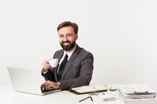 Glücklicher attraktiver bärtiger geschäftsmann mit kurzen braunen haaren, die tasse tee halten und freudig nach vorne schauen, mit laptop arbeiten und brief an seine partner tippen
