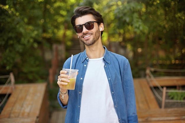 Glücklicher attraktiver dunkelhaariger mann im blauen hemd, der über grünen bäumen am sonnigen tag steht, guten tag hat und limonade im öffentlichen platz im freien trinkt