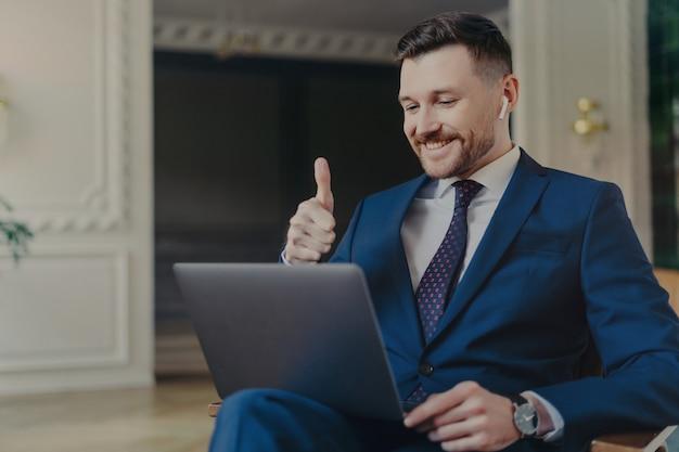 Glücklicher attraktiver geschäftsprofi in elegantem anzug, der seine zufriedenheit durch geste daumen nach oben während der videokonferenz mit dem chef oder kollegen auf dem laptop zeigt, die in einem modernen hellen büro arbeiten