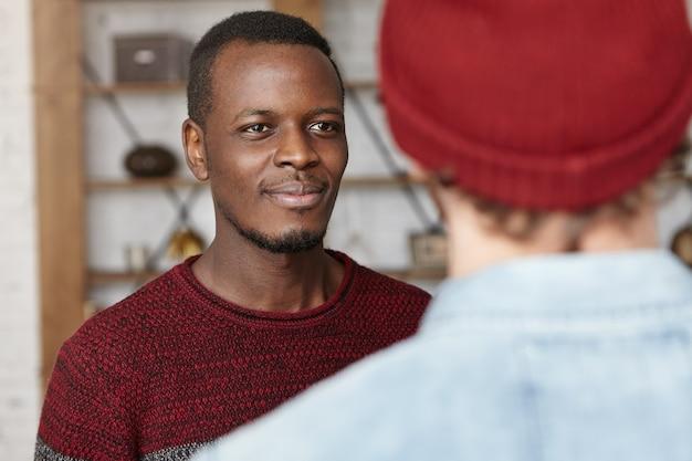 Glücklicher attraktiver junger afroamerikaner, der fröhlich lächelt, während er gute unterhaltung hat