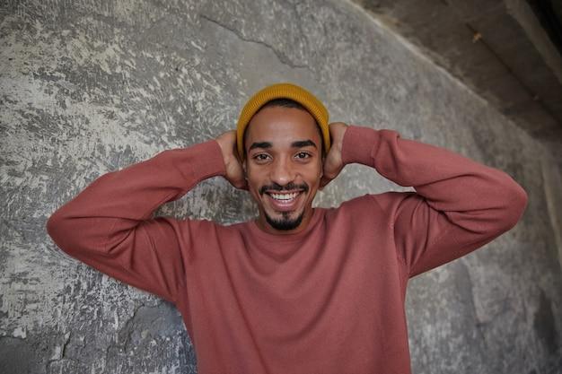 Glücklicher attraktiver junger bärtiger dunkelhäutiger mann mit charmantem lächeln, das fröhlich schaut und seinen kopf mit erhobenen händen hält, in hochstimmung ist, während er über betonmauer steht