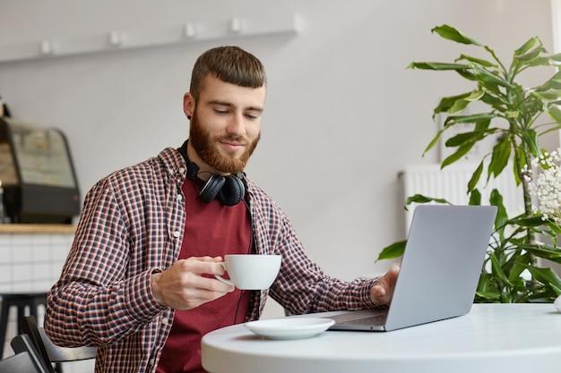 Glücklicher attraktiver junger bärtiger mann des ingwers, der an einem laptop arbeitet, in einem café sitzt, in der grundkleidung trägt, lächelt und den kaffee genießt.