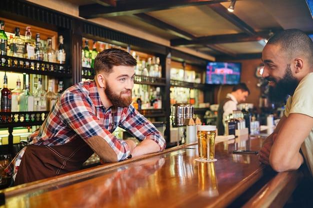 Glücklicher attraktiver junger barmann, der ein glas bier gibt und mit jungem mann spricht