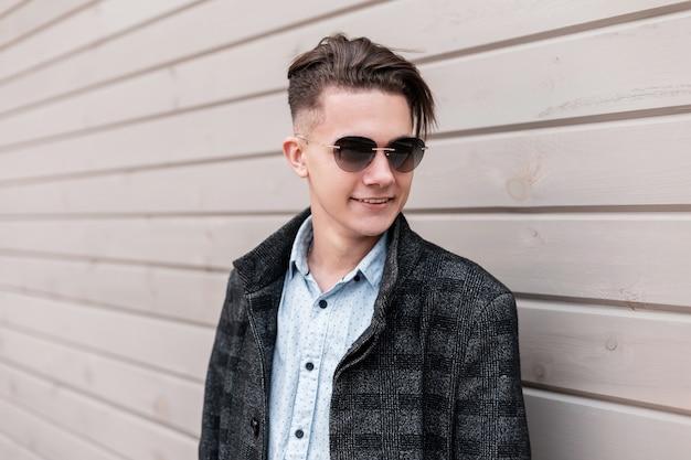 Glücklicher attraktiver junger hipster-mann in der dunklen trendigen sonnenbrille in einer grauen karierten jacke mit einer modischen frisur in einem hemd nahe einer holzwand