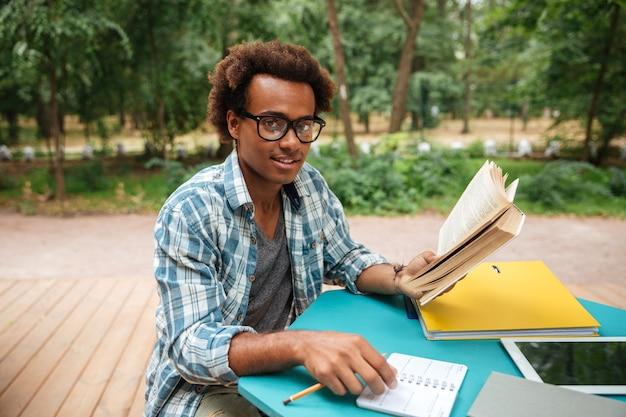 Glücklicher attraktiver junger mann, der draußen studiert