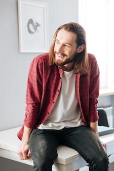 Glücklicher attraktiver junger mann, der zu hause auf dem tisch sitzt