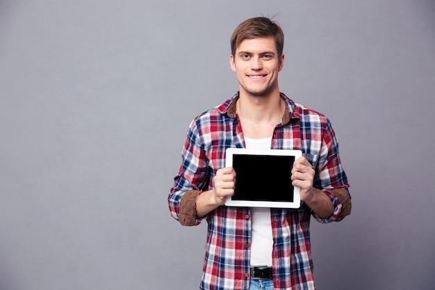 Glücklicher attraktiver junger mann im karierten hemd, der ein leeres bildschirmtablett über grauer wand steht und hält