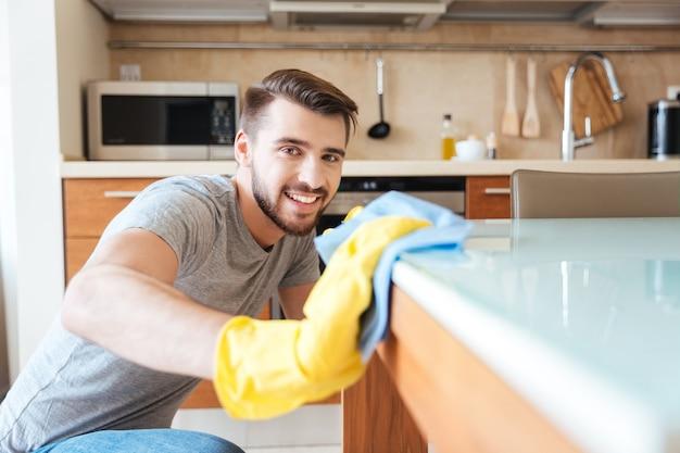 Glücklicher attraktiver junger mann in gelben handschuhen, der die küche mit lappen säubert