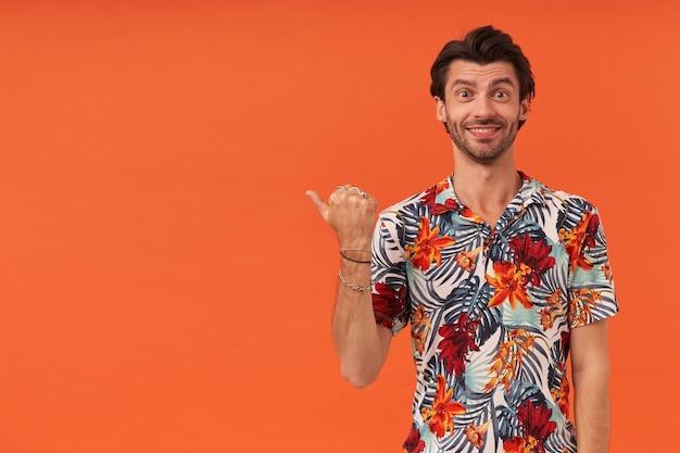 Glücklicher attraktiver junger mann mit borste im hawaiianischen hemd, das zur seite am kopyspace durch daumenfinger zeigt