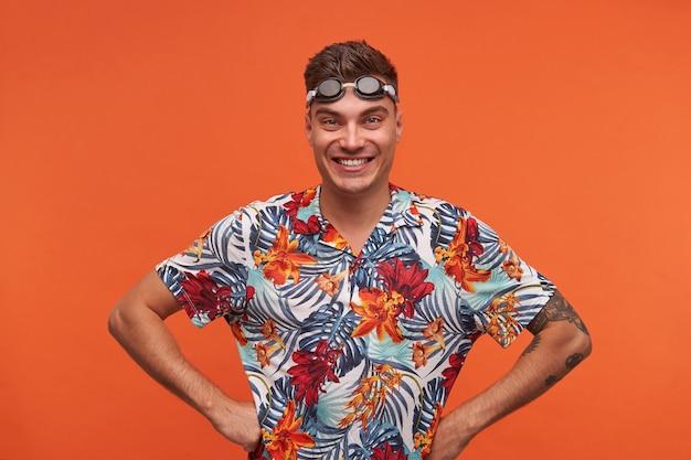 Glücklicher attraktiver junger schwimmer mit schutzbrille auf seiner stirn stehend, freudig mit den händen auf den hüften schauend