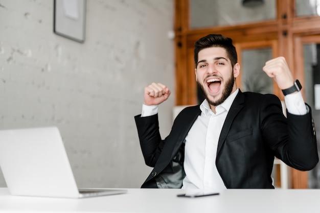 Glücklicher attraktiver kerl am arbeitsplatz mit laptop im büro