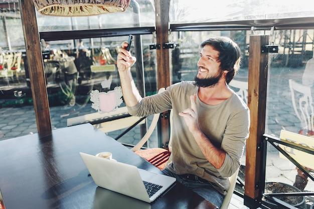Glücklicher attraktiver kerl, der das selfie zeigt siegesgeste und -c $ lächeln macht. café im freien hintergrund