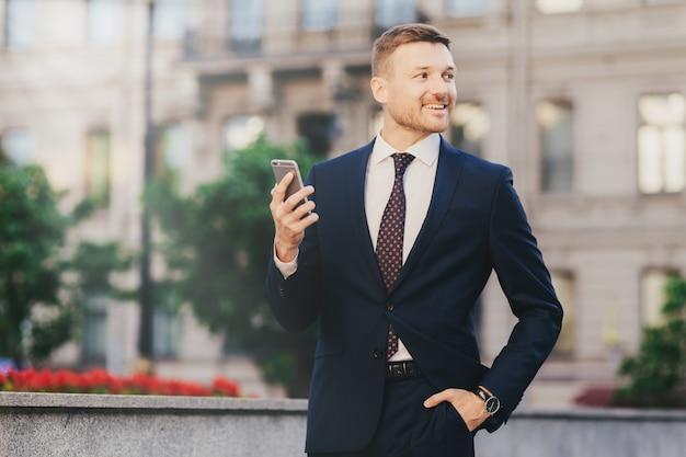 Glücklicher attraktiver männlicher finanzier in der eleganten abnutzung, unter verwendung des modernen smartphone