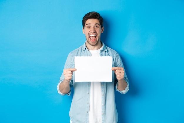Glücklicher attraktiver mann, der ein stück papier für ihr logo-zeichen zeigt und erstaunt vor blauem hintergrund steht