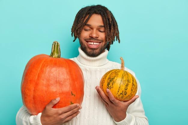 Glücklicher attraktiver mann mit angenehmem lächeln, hält großen und kleinen kürbis, wählt produkt für das vorbereiten der köstlichen gemüsecremesuppe