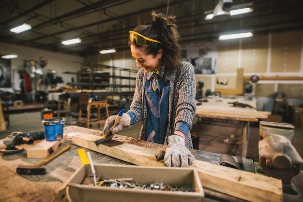 Glücklicher attraktiver professioneller weiblicher arbeiter, der holz mit schwarzer farbe in der sonnigen werkstatt malt