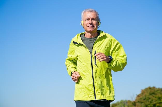 Glücklicher aufgeregter älterer mann in drahtlosen kopfhörern, die draußen joggen. niedriger winkel, blauer klarer himmel. vorderansicht, kopierraum. aktivitäts- und alterskonzept