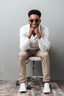 Glücklicher aufgeregter afroamerikanischer mann im sonnenbrillensitzen
