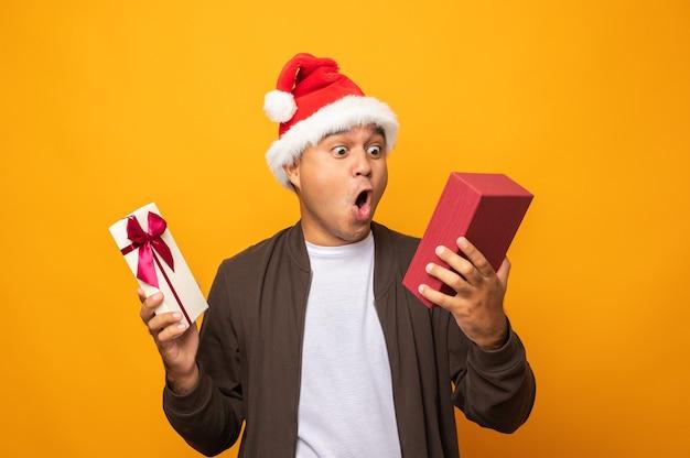 Glücklicher aufgeregter asiatischer mann am weihnachtstag, der die gegenwärtige geschenkbox hält.