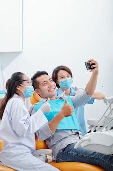 Glücklicher aufgeregter asiatischer mann, der mit zahnarzt und assistentin lächelt und selfie macht