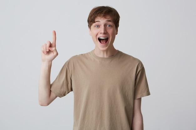 Glücklicher aufgeregter blonder junger mann mit kurzem haarschnitt und zahnspangen trägt beige t-shirt und zeigt nach oben
