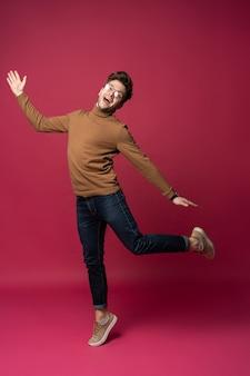 Glücklicher aufgeregter fröhlicher junger mann, der springt und erfolg lokalisiert auf einem rosa hintergrund feiert.